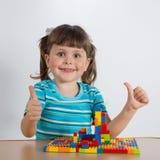 使用与连接的玩具立方体的女孩 免版税库存图片