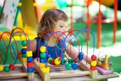 使用与迷宫教育玩具的小女孩 免版税库存图片