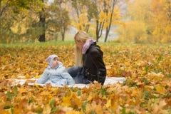 使用与逗人喜爱的一个年小孩的愉快的母亲在秋天公园 免版税库存图片