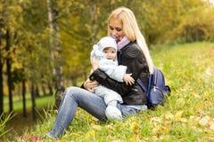 使用与逗人喜爱的一个年小孩的愉快的母亲在秋天公园 免版税库存照片