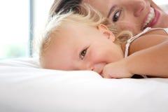 使用与逗人喜爱的女婴的微笑的母亲 免版税库存图片