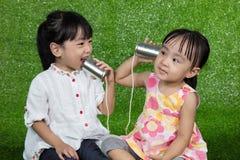 使用与锡罐电话的亚洲中国孩子 免版税库存照片