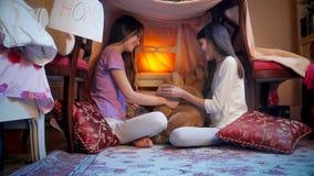 使用与长毛绒的两个愉快的女孩在帐篷戏弄在卧室在晚上 库存照片