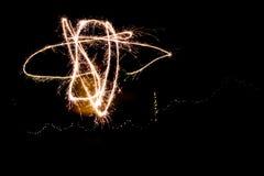 使用与闪烁发光物的一个少妇在创造任意的晚上 库存照片
