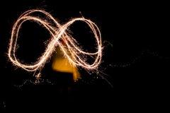 使用与闪烁发光物的一个少妇在创造infini的晚上 库存图片