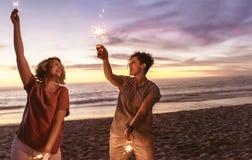 使用与闪烁发光物的笑的朋友在海滩在日落期间 免版税库存图片