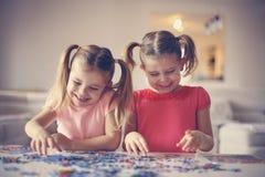 使用与难题的两个小女孩 黑色接近的耳机图象软绵绵地查出话筒填充白色 免版税图库摄影