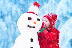 使用与雪人的小女孩 免版税库存图片