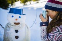 使用与雪人的愉快的微笑的十几岁的女孩 免版税图库摄影