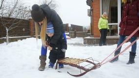 使用与雪撬的逗人喜爱的男婴慢动作录影在房子后院 股票录像
