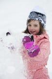 使用与雪的一个愉快的小女孩 免版税库存照片