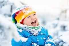 使用与雪的婴孩在冬天 孩子在多雪的公园 免版税库存图片