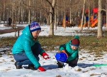 使用与雪的母亲和儿子 免版税库存图片