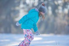 使用与雪的温暖的衣物的愉快的年轻青春期前的女孩 免版税库存照片