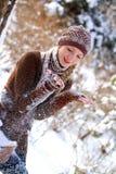 使用与雪的逗人喜爱的女孩在冬天公园 免版税库存图片