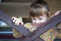 使用与青蛙蟾蜍和笑的一个逗人喜爱的幼儿女孩 免版税库存图片