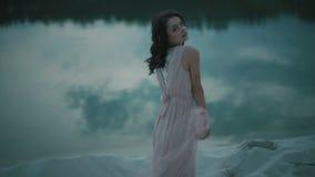 使用与面纱和接触她的面孔的浅粉红色的礼服的年轻性深色的女孩,当摆在含沙岸时 股票录像