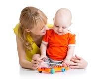 使用与音乐玩具的微笑的孩子和妈妈 免版税库存图片