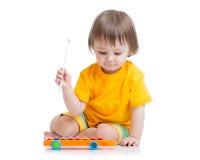 使用与音乐玩具的微笑的孩子 库存图片