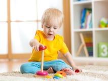 使用与颜色玩具的逗人喜爱的孩子室内 免版税库存图片