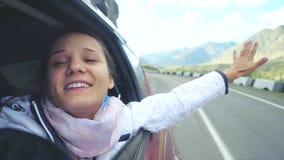 使用与风和驾驶通过美丽的山的汽车的微笑的年轻深色的妇女 3840x2160 股票视频