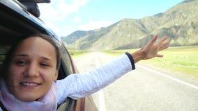 使用与风和驾驶通过美丽的山的汽车的微笑的年轻深色的妇女 3840x2160 股票录像