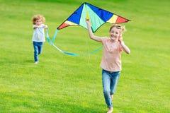 使用与风筝的愉快的逗人喜爱的兄弟姐妹,当跑在绿色草坪时 免版税库存图片