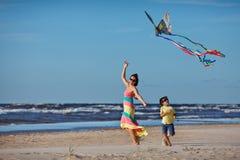 年轻使用与风筝的mather和她的儿子 免版税图库摄影