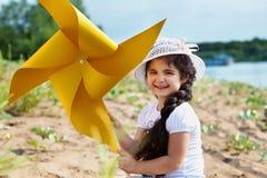 使用与风车的快乐的深色头发的女孩 免版税库存照片