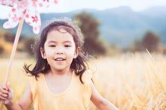 使用与风轮机的逗人喜爱的亚裔小孩女孩 免版税库存图片