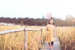 使用与风轮机的逗人喜爱的亚裔小孩女孩 库存图片