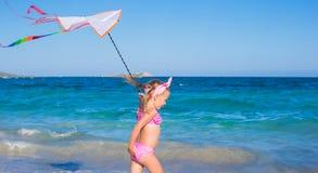 使用与飞行风筝的小可爱的女孩  免版税库存照片