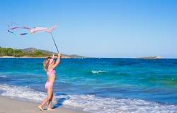使用与飞行风筝的小愉快的女孩在期间 库存图片