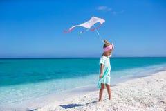 使用与飞行风筝的小愉快的女孩  库存照片