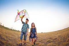 使用与飞行风筝的愉快的孩子在夏天调遣 库存图片