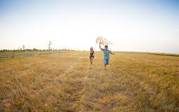 使用与飞行风筝的愉快的孩子在夏天调遣 库存照片