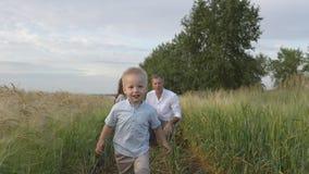 使用与麦田的孩子的愉快的父母 免版税库存照片