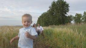 使用与麦田的孩子的愉快的父母 免版税库存图片