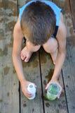 使用与水和容器的男孩 免版税图库摄影
