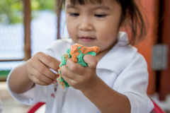 使用与黏土的儿童逗人喜爱的小女孩 免版税库存图片