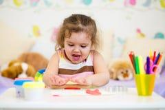 使用与黏土的孩子女孩户内 免版税库存照片