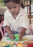使用与黏土,戏剧C大调的第1音的儿童逗人喜爱的小女孩 免版税库存图片