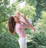 使用与婴孩的一个愉快的母亲的画象在公园 免版税库存图片