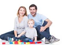 使用与婴孩的微笑的年轻家庭。 免版税库存照片