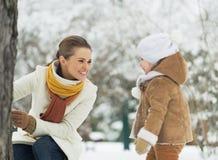 使用与婴孩的愉快的母亲在冬天公园 库存图片