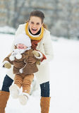使用与婴孩的愉快的母亲在冬天公园 图库摄影