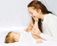 使用与婴孩的愉快的片刻母亲在床上 免版税图库摄影
