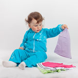 使用与婴孩的蓝色连裤外衣的婴孩穿衣 图库摄影