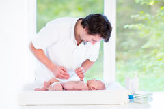 使用与他新出生的小儿子的年轻愉快的父亲 免版税库存图片