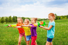使用与水枪的四个孩子 免版税库存照片